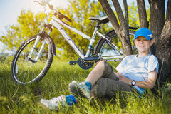 Happy kid with a bicycle resting under a tree Stock Photography