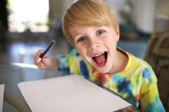 Happy Kid with Big Smile Drawing on White Paper with Pen Stock Images