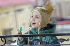 Blowing Bubbles. Happy kid blowing bubbles on a terrace royalty free stock photo