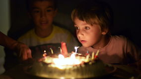 Happy kid blowing candles at his anniversary. Happy kid blowing candles at his four years anniversary stock footage