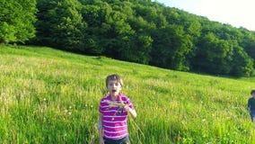 Happy Kid Blowing Dandelion Flower. Slow motion stock footage
