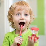 Happy kid boy brushing teeth in bathroom. He is monitoring lasting of cleaning action with hourglass. stock image