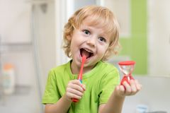 Happy child boy brushing teeth near mirror in bathroom. He is monitoring lasting of cleaning action with hourglass. Happy kid boy brushing teeth near mirror in stock photo