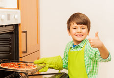 Happy kid boy cooking homemade pizza in the oven Stock Photos