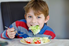 Happy kid boy eating fresh salad with tomato, cucumber and different vegetables as meal or snack. Healthy child enjoying. Tasty and fresh food at home or at royalty free stock images