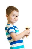 Happy kid boy eating icecream in studio isolated Royalty Free Stock Images