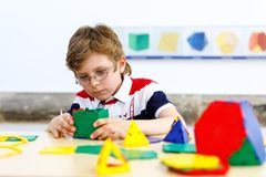 Happy kid boy with glasses having fun with building and creating geometric figures, learning mathematics and geometry. Little kid boy with glasses playing with stock image