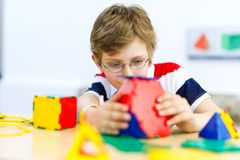 Happy kid boy with glasses having fun with building and creating geometric figures, learning mathematics and geometry. Little kid boy with glasses playing with royalty free stock photography