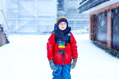Happy kid boy with glasses having fun with snow on way to school, elementary class royalty free stock photography