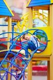 Happy kid, boy having fun on playground in park royalty free stock photo