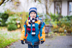 Happy kid boy having fun with snow on way to school Royalty Free Stock Image