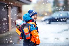 Happy kid boy having fun with snow on way to school Royalty Free Stock Images
