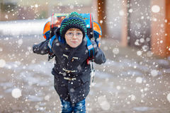 Happy kid boy having fun with snow on way to school Stock Image