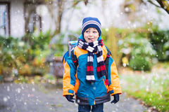Happy kid boy having fun with snow on way to school Royalty Free Stock Image