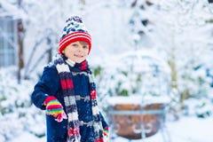 Happy kid boy having fun with snow in winter stock image