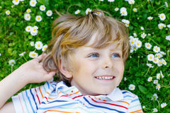 Happy kid boy laying on green grass in summer Royalty Free Stock Photos