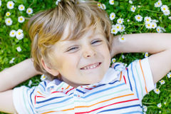 Happy kid boy laying on green grass in summer. Happy little blond child with blue eyes laying on the grass with daisies flowers in the park. On warm summer day Stock Images