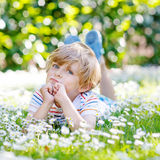 Happy kid boy laying on green grass in summer. Happy little blond child with blue eyes laying on the grass with daisies flowers in the park. On warm summer day Royalty Free Stock Photo