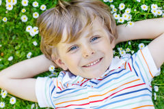 Happy kid boy laying on green grass in summer. Happy little blond child with blue eyes laying on the grass with daisies flowers in the park. On warm summer day Stock Photo