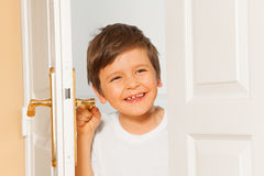 Happy kid boy looking through the doorway Royalty Free Stock Images
