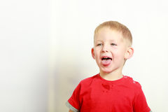 Happy kid boy making funny silly faces. Face expressions, children concept. Portrait of happy kid boy making funny silly faces Royalty Free Stock Photography