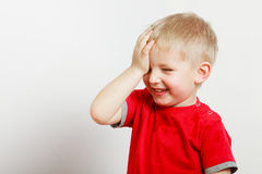 Happy kid boy making funny silly faces. Face expressions, children concept. Portrait of happy kid boy making funny silly faces with hand on forehead stock photography