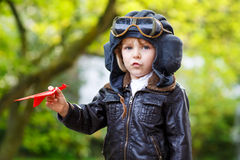 Happy kid boy in pilot helmet playing with toy airplane Stock Images