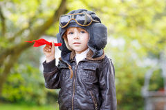 Happy kid boy in pilot helmet playing with toy airplane Royalty Free Stock Image