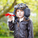 Happy kid boy in pilot helmet playing with toy airplane Royalty Free Stock Images