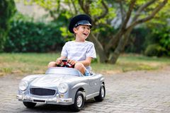 Happy kid boy playing with big old toy car in summer garden, outdoors. Healthy child driving old vintage car taxi Royalty Free Stock Photos