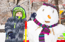 Happy kid boy playing with a snowman on winter walk in nature. Child having fun at Christmas time outdoor. Royalty Free Stock Photography