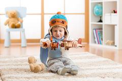Happy kid boy playing with toy airplane at home in his room Royalty Free Stock Photos