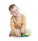 Happy kid boy playing with train toy isolated. On white Stock Photography