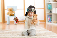 Happy kid boy plays with toy airplane at home in his room Stock Photo