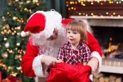 Happy kid boy pulls gift out Santa Claus sack Stock Photos