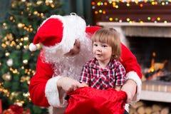 Happy kid boy pulls gift out Santa Claus sack Stock Photos