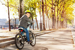 Happy kid boy riding his bike on cycle lane. In autumn town royalty free stock images