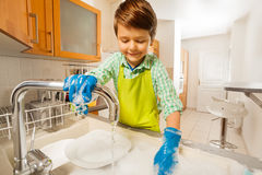 Happy kid boy rinsing dishes in the sink. Portrait of happy kid boy rinsing dishes under running water in the sink in the kitchen Stock Photography