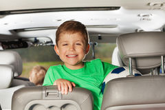 Happy kid boy sitting in the car and holding ball Stock Photo