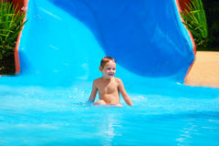 Happy kid boy sliding in tropical water park Royalty Free Stock Photo