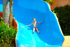 Happy kid boy sliding in tropical water park Stock Photos