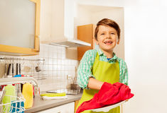 Happy kid boy wiping dry plate with red dish towel. Portrait of happy kid boy standing in the kitchen and wiping dry plate with red towel Royalty Free Stock Photo
