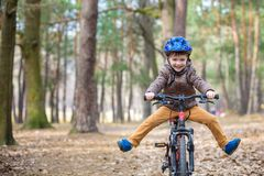 Happy kid boy of 3 or 5 years having fun in autumn forest with a bicycle on beautiful fall day. Active child wearing bike helmet. Safety, sports, leisure with royalty free stock images