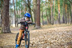 Happy kid boy of 3 or 5 years having fun in autumn forest with a. Bicycle on beautiful fall day. Active child wearing bike helmet. Safety, sports, leisure with Royalty Free Stock Images