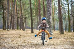 Happy kid boy of 3 or 5 years having fun in autumn forest with a bicycle on beautiful fall day. Active child wearing bike helmet. Safety, sports, leisure with royalty free stock photos