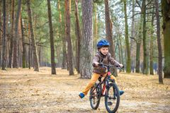 Happy kid boy of 3 or 5 years having fun in autumn forest with a bicycle on beautiful fall day. Active child wearing bike helmet. Safety, sports, leisure with stock photography