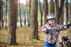 Happy kid boy of 3 or 5 years having fun in autumn forest with a. Bicycle on beautiful fall day. Active child wearing bike helmet. Safety, sports, leisure with Stock Image