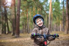 Happy kid boy of 3 or 5 years having fun in autumn forest with a. Bicycle on beautiful fall day. Active child wearing bike helmet. Safety, sports, leisure with Royalty Free Stock Photos