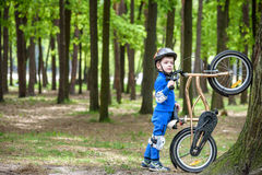 Happy kid boy of 4 years having fun in autumn or summer forest with a bicycle Royalty Free Stock Photo