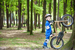 Happy kid boy of 4 years having fun in autumn or summer forest with a bicycle Stock Photos